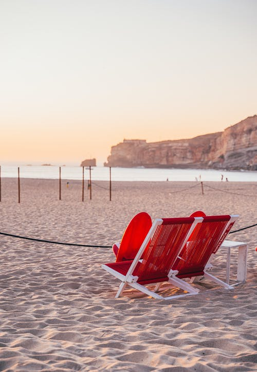 Two Red-and-white Folding Chairs on Sand