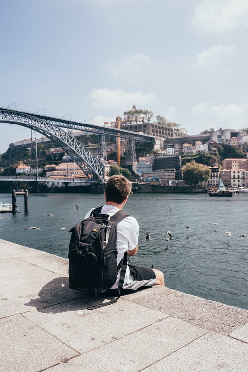 Back view of anonymous male tourist with backpack admiring cityscape on other side of river and openwork metal structure of bridge over river on sunny day