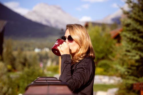 Shallow Focus Photo of Woman in Black Long-sleeved Shirt Drinking on Maroon Ceramic Mug