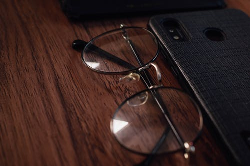 Photo Of Eyeglasses Beside Smart Phone