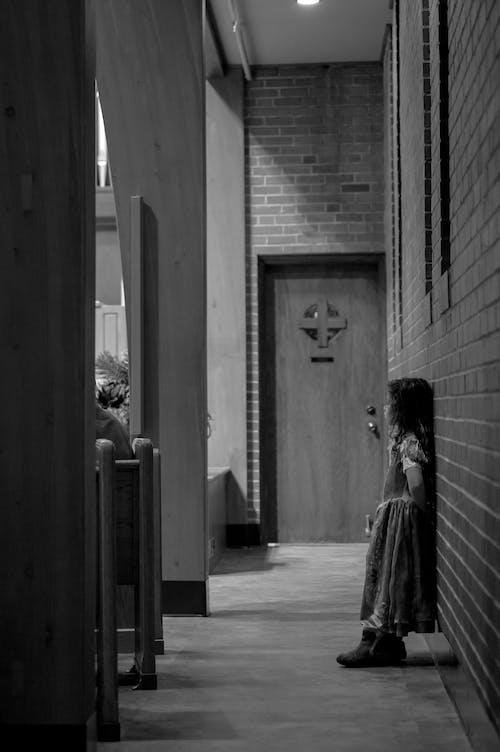 Grayscale Photo of Child in Dress Standing in Front of Door