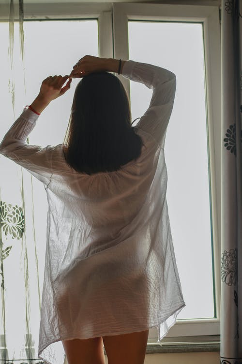 Back view of anonymous slim sensitive female in transparent wear standing with raised arms near window in flat