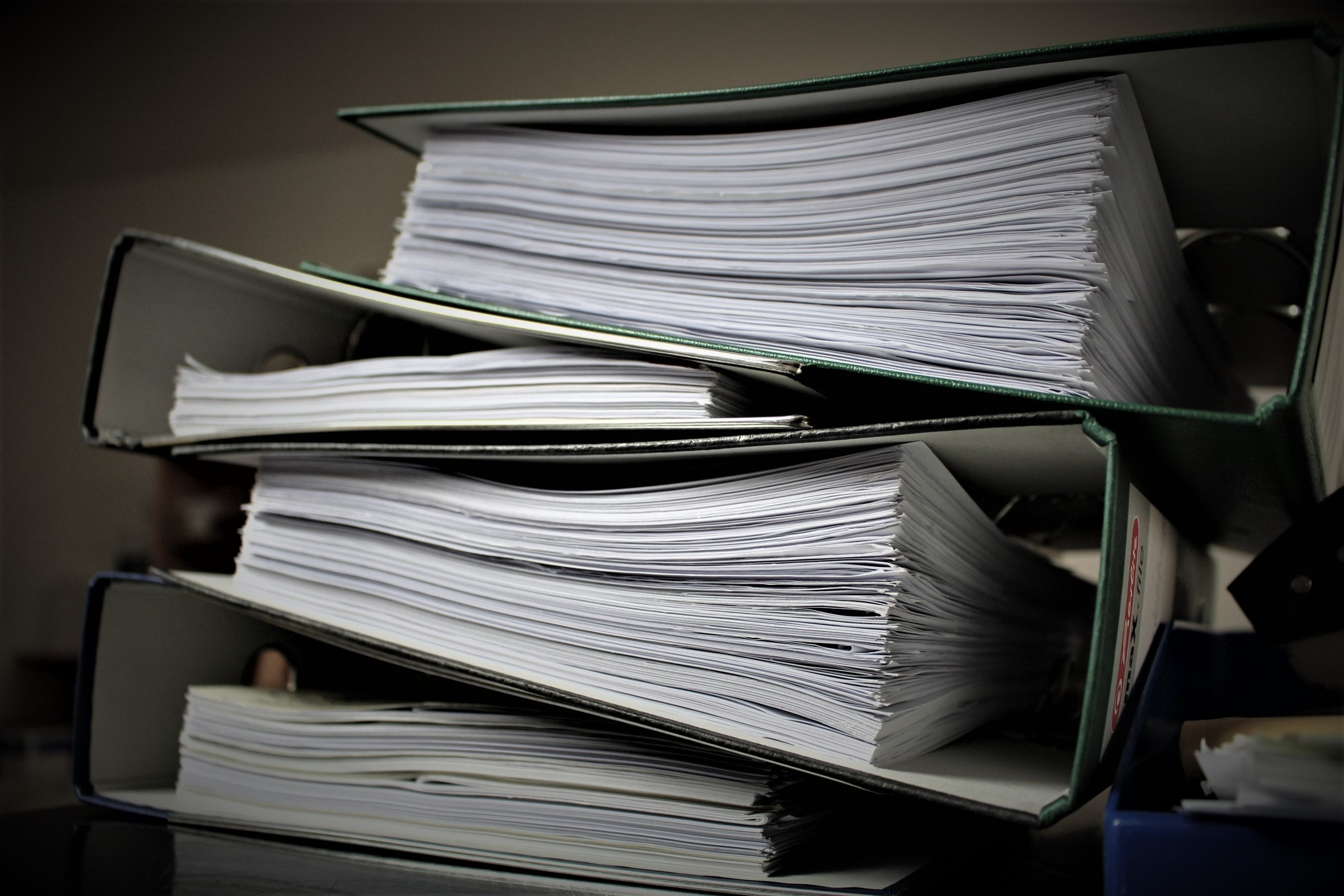 Three binders with piles of paper contained inside of them.