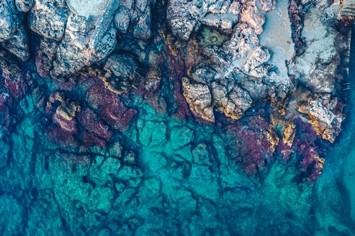 Aerial Photography of Rocks Beside Body of Water