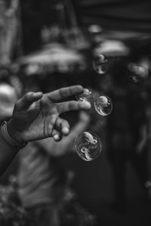 Grayscale Photo Of Person Touching Bubbles
