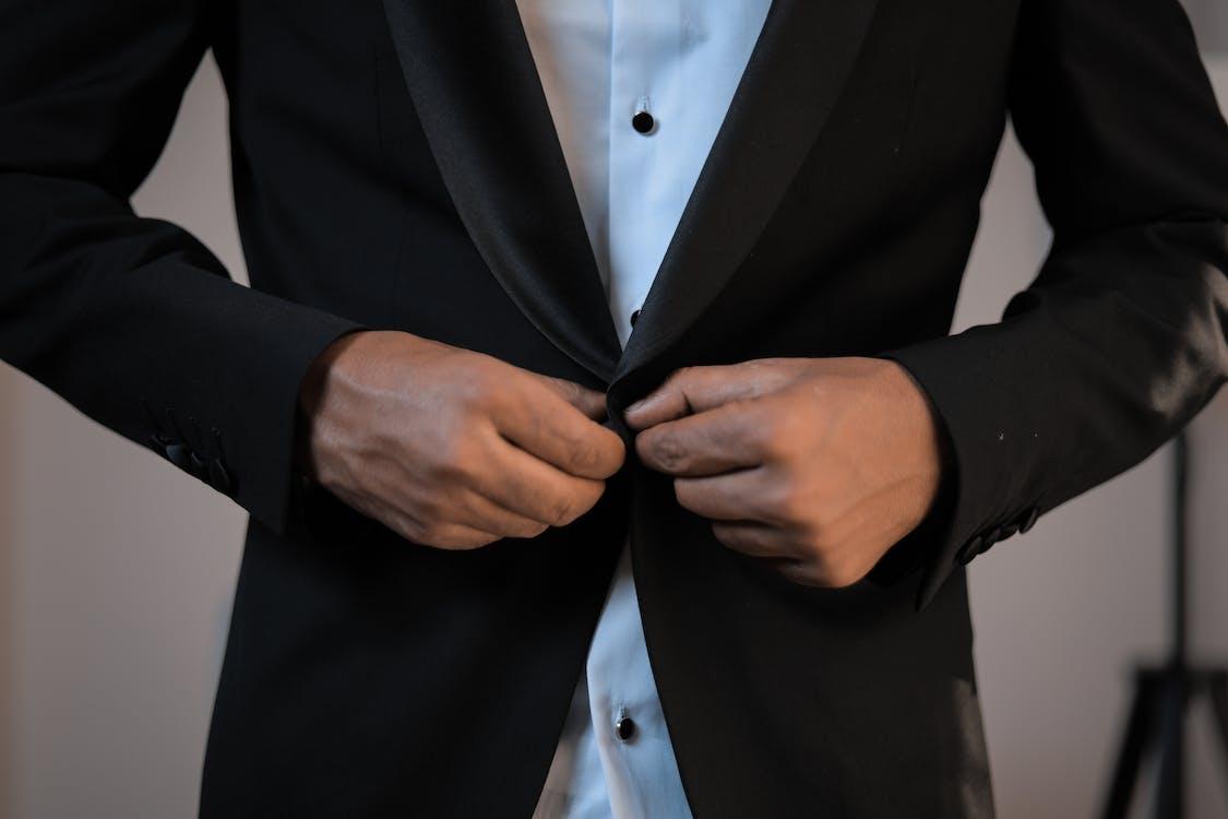 Businessman buttoning up blazer of elegant suit