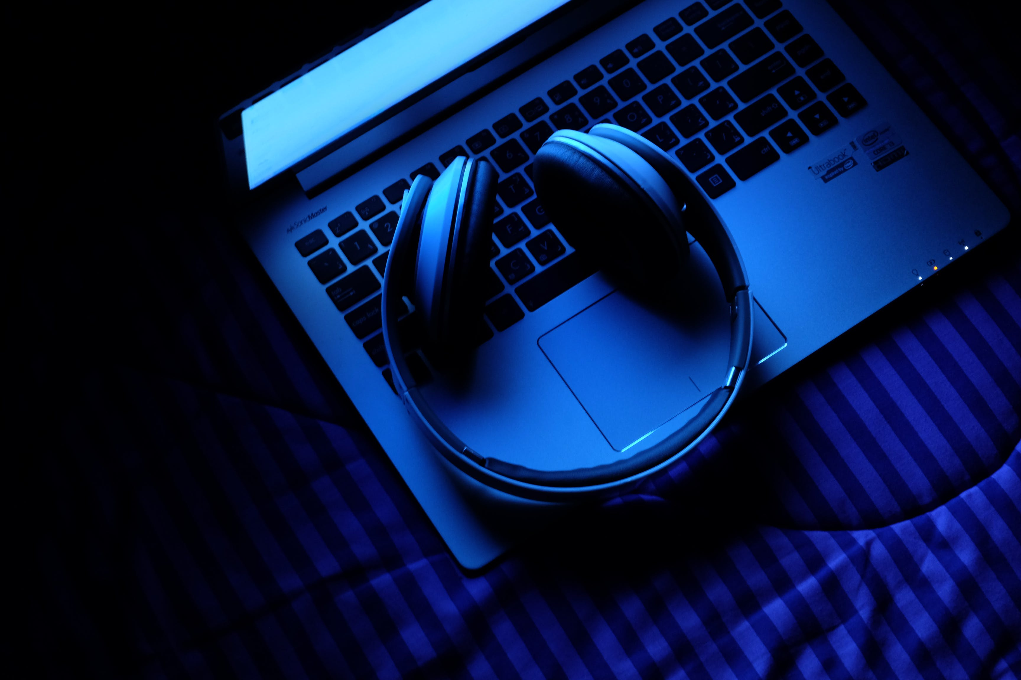 Foto profissional grátis de caderno, computador portátil, fones de ouvido, música