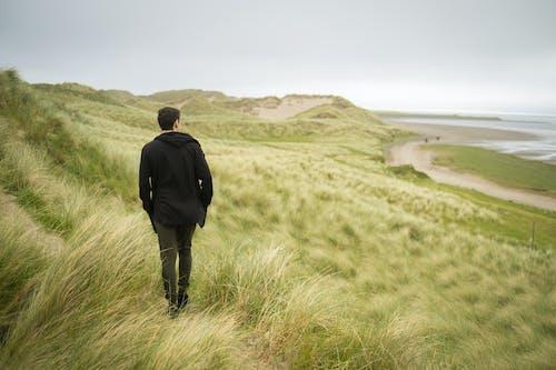 Man in Black Jacket Walking on Green Grass Field