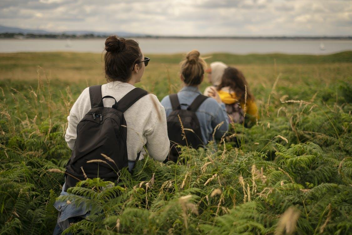 People Wearing Backpack Walking in Grass Field