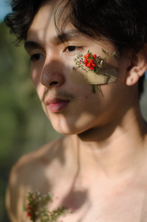 Man With Red Flower Attached on Cheek
