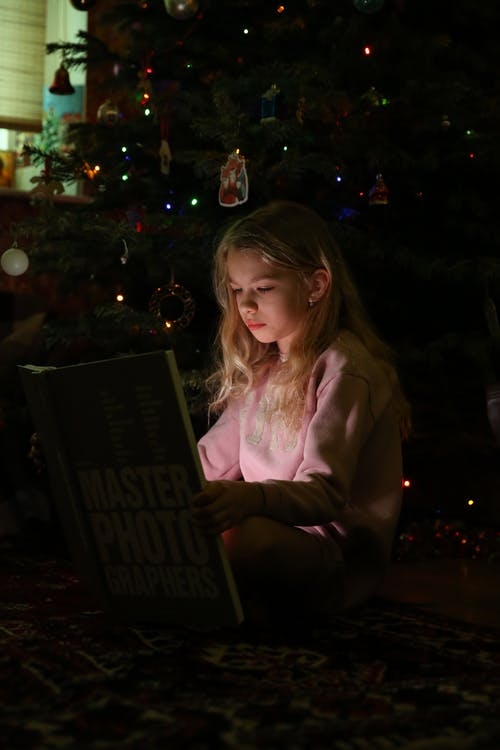 Girl in Pink Hoodie Holding Book