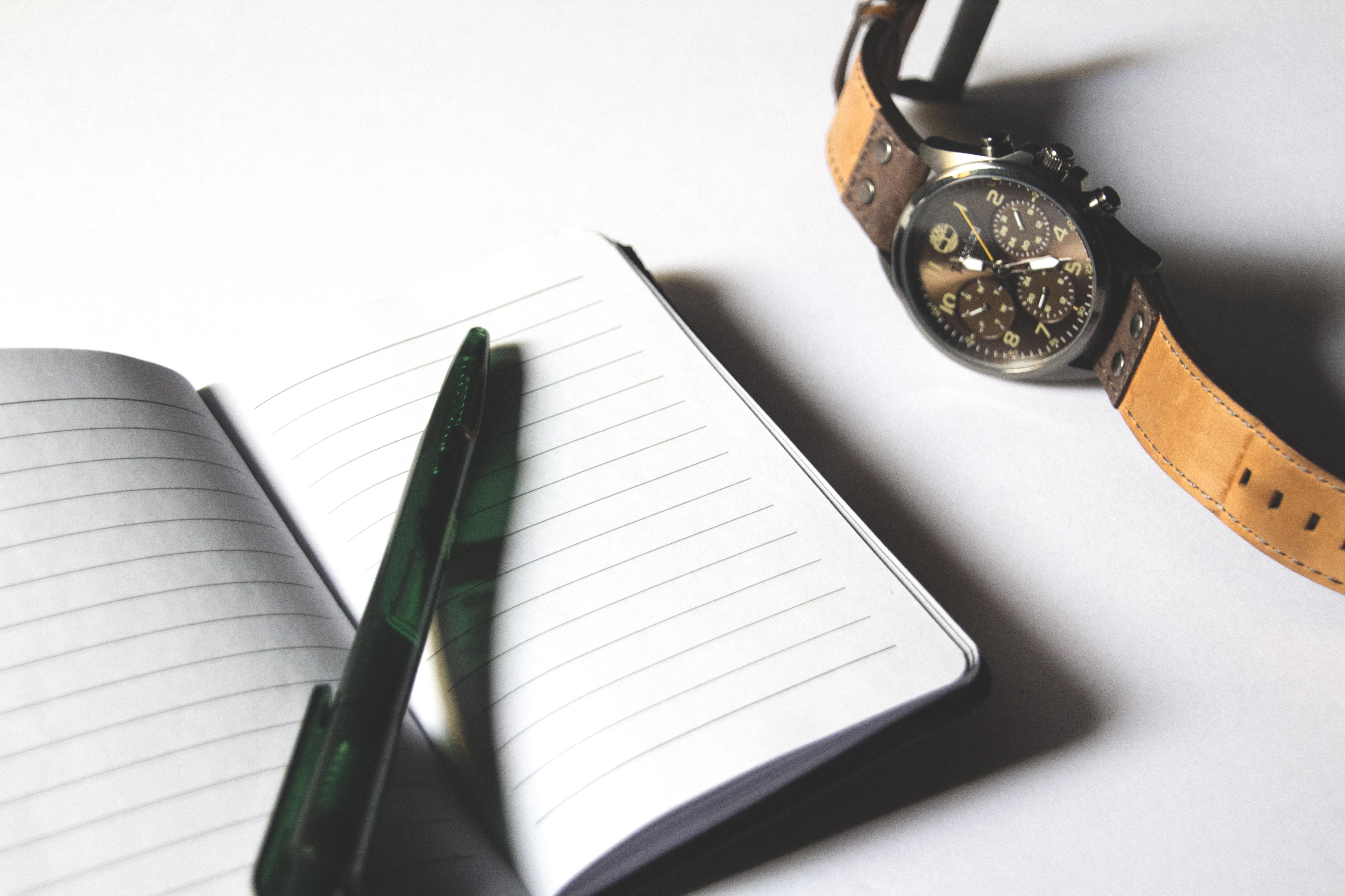 Click Pen on Notebook Beside Chronograph Watch