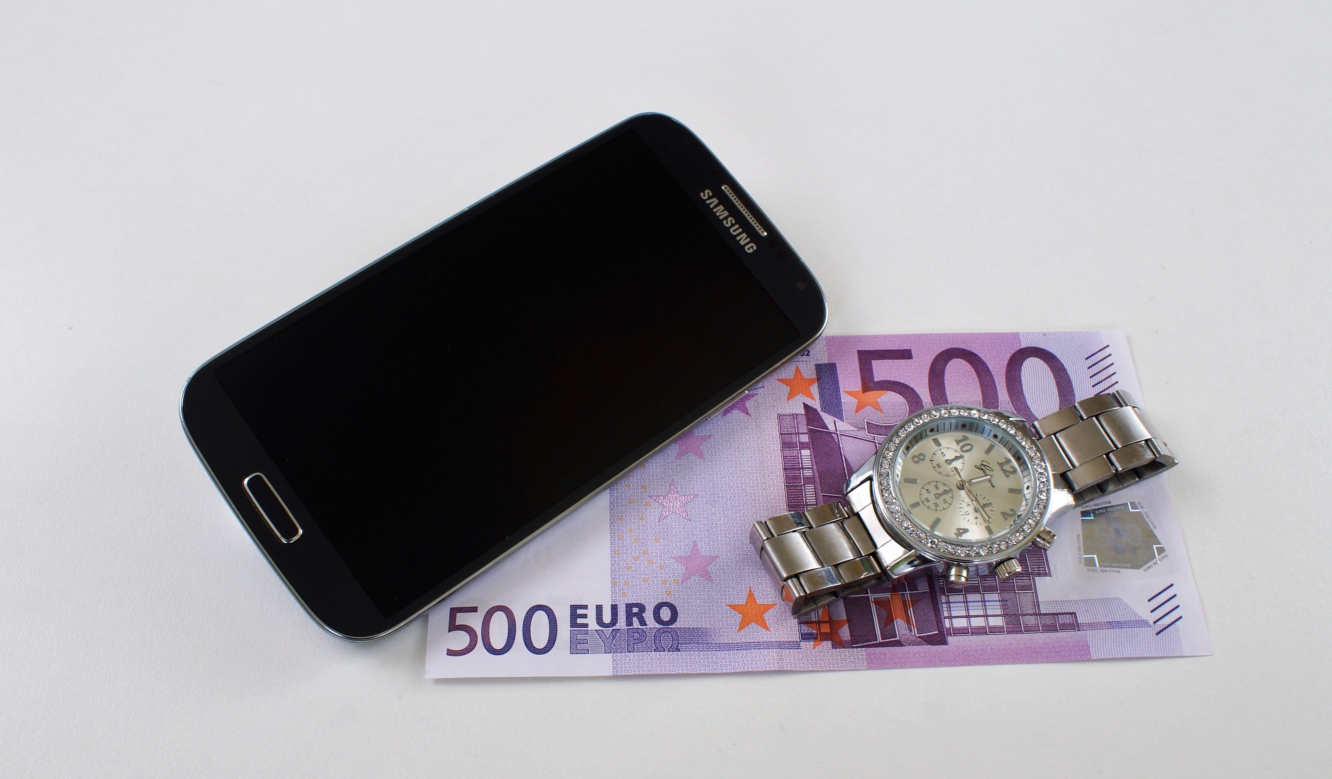 Black Samsung Galaxy Smartphone Beside Silver-colored Watch