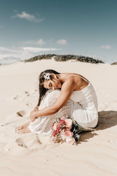 Woman Sitting on White Sand