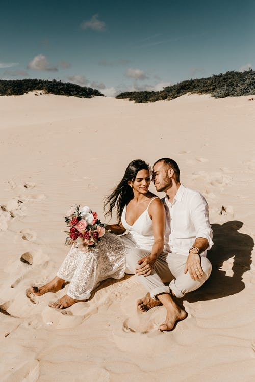Photo Of Couple Sitting On Sand