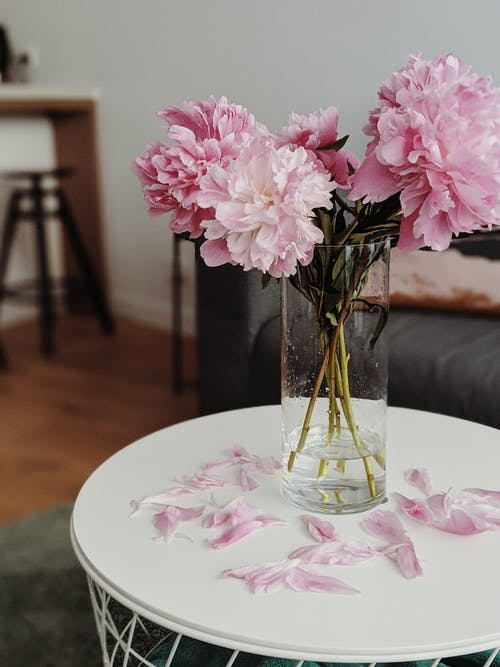 Pink Flowers In Clear Glass Vase On White Round Table