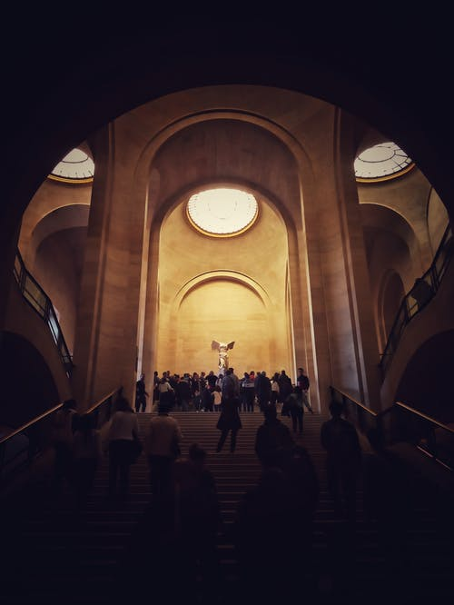 From below of people standing on dark stairs and light majestic hall of modern building with tall arched ceilings and round windows at top
