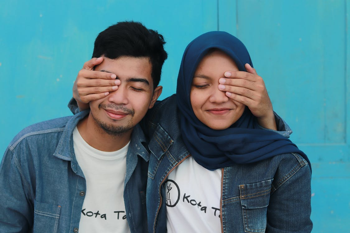 Man in Blue Denim Jacket Beside Woman in Blue Hijab