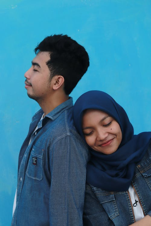 Man in Blue Denim Jacket Beside Woman in Blue Hijab