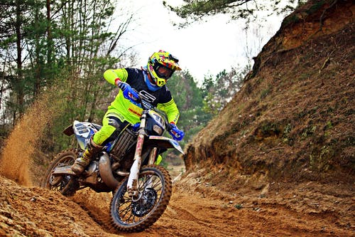 Man Riding Blue and White Dirt Bike