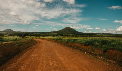 Photo of Dirt Road Across Hill Under Cloudy Sky