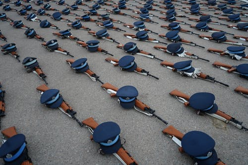 Photo of Blue Caps and Rifles on Floor