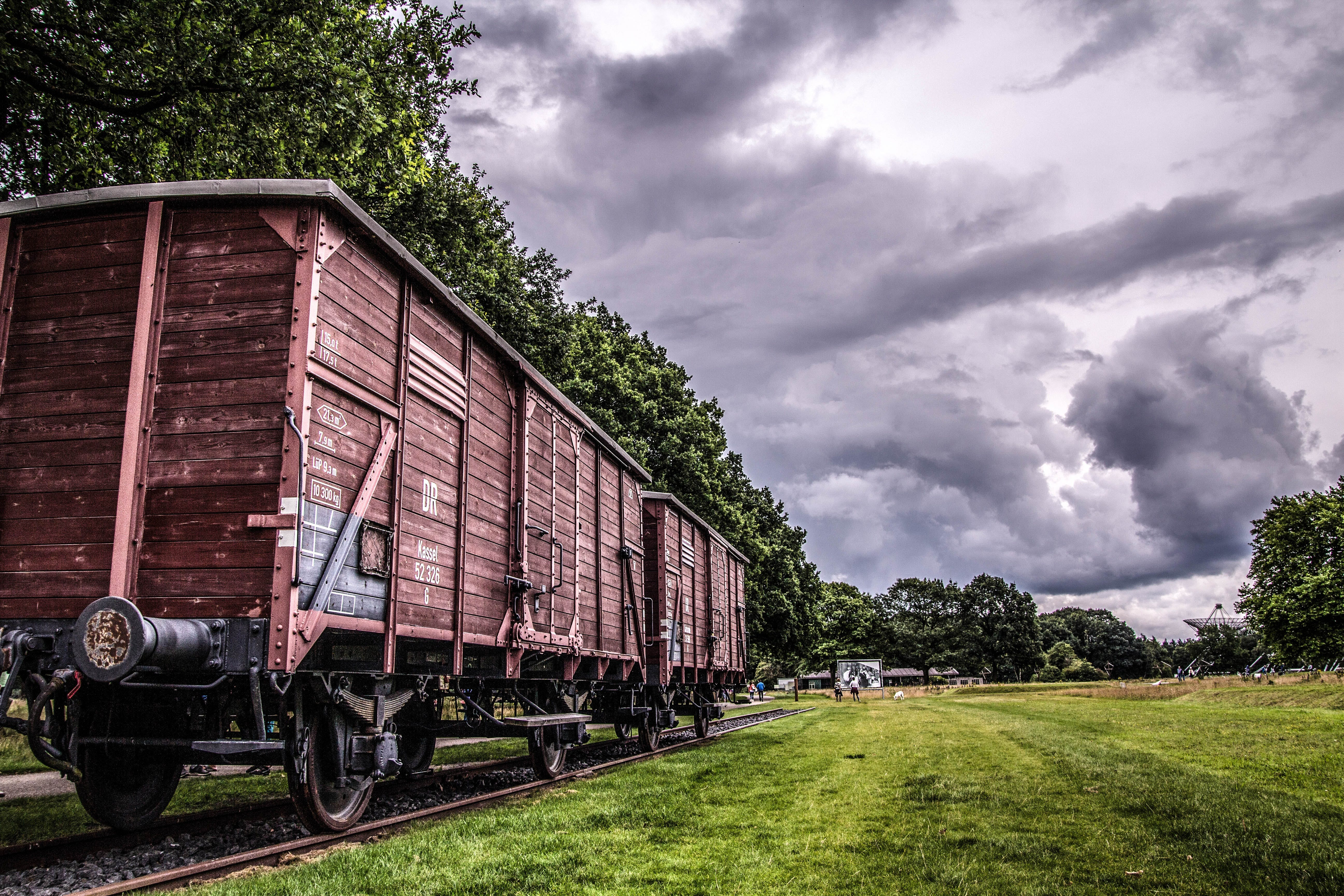 Two Train Cars on Track Under Cloudy Sky