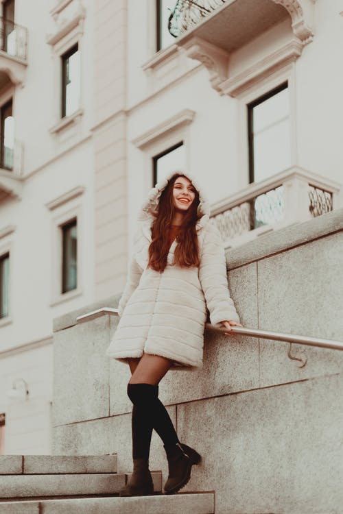Woman Wearing White Coat Leaning on Handrail