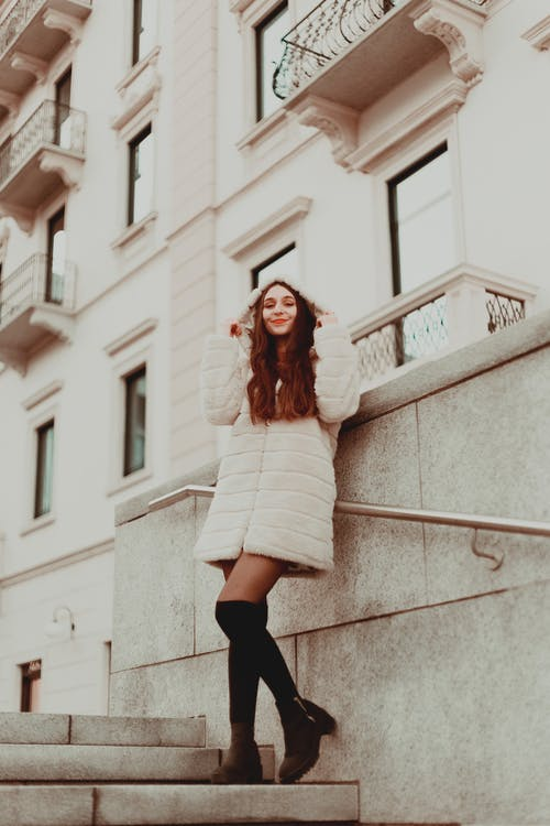 Woman Wearing White Fur Coat While Leaning on Handrail