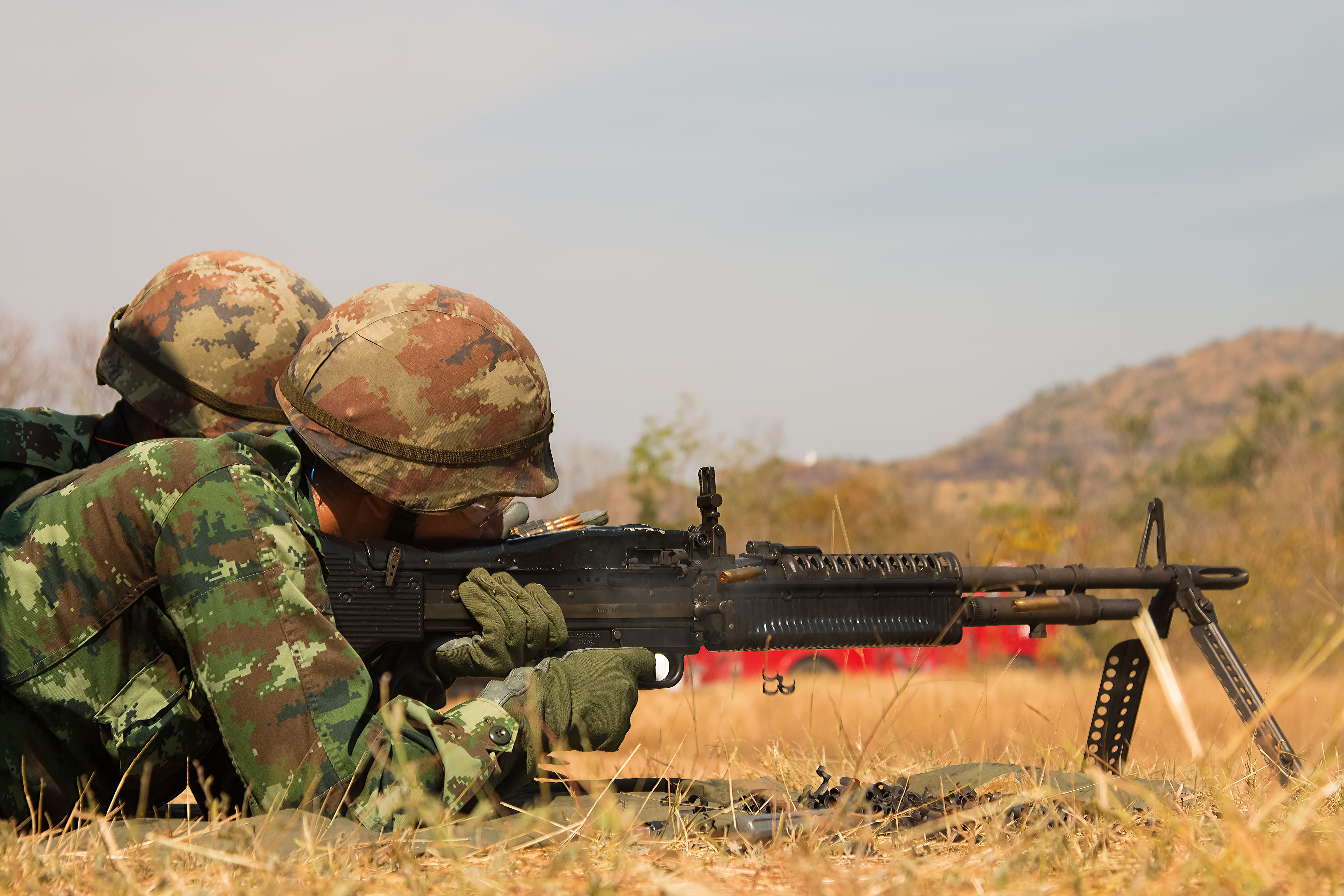 Man Lying Forward Using Rifle at the Field during Day