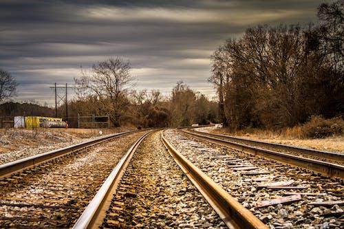 Бесплатное стоковое фото с гравий, деревья, дорога, железнодорожные пути