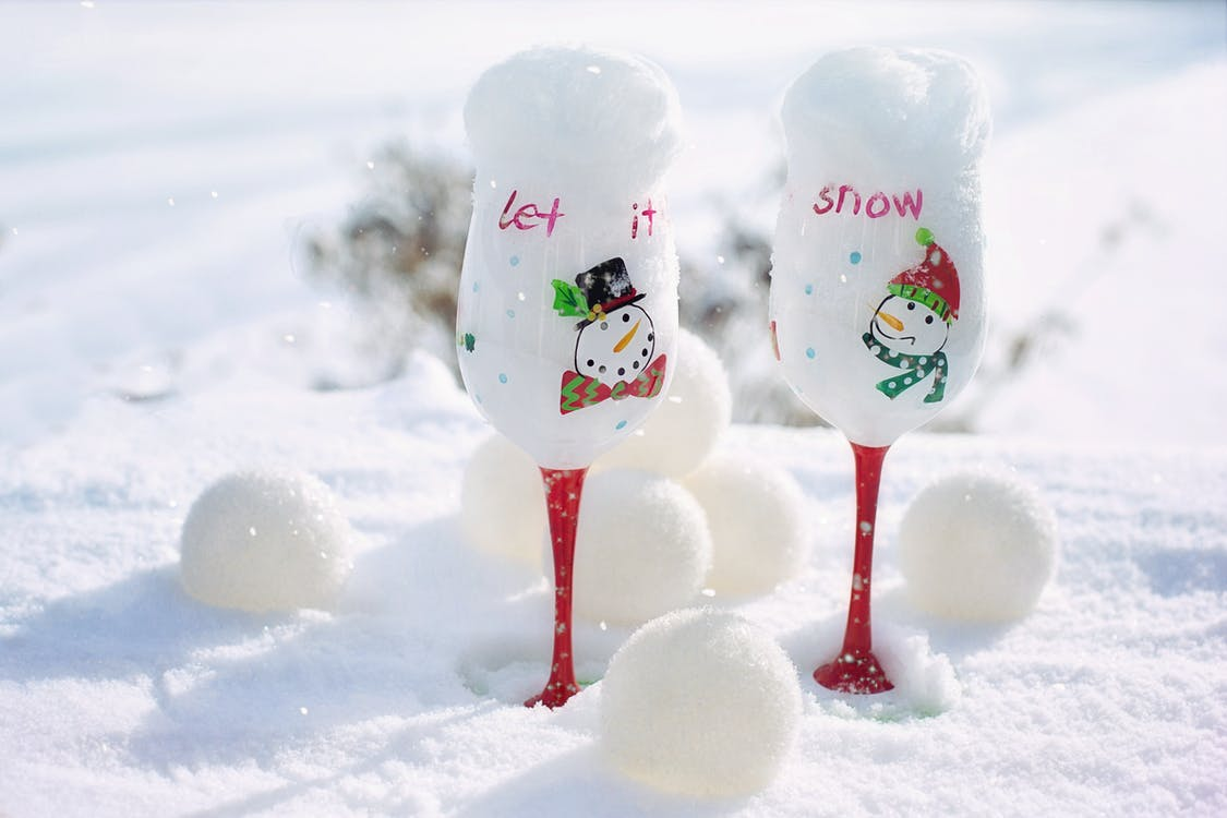 Two White-and-red Snowman-printed Wine Glasses on Snow