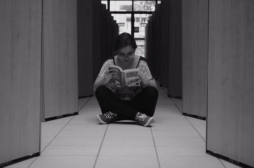 Woman Sitting on Floor Tile While Reading a Book