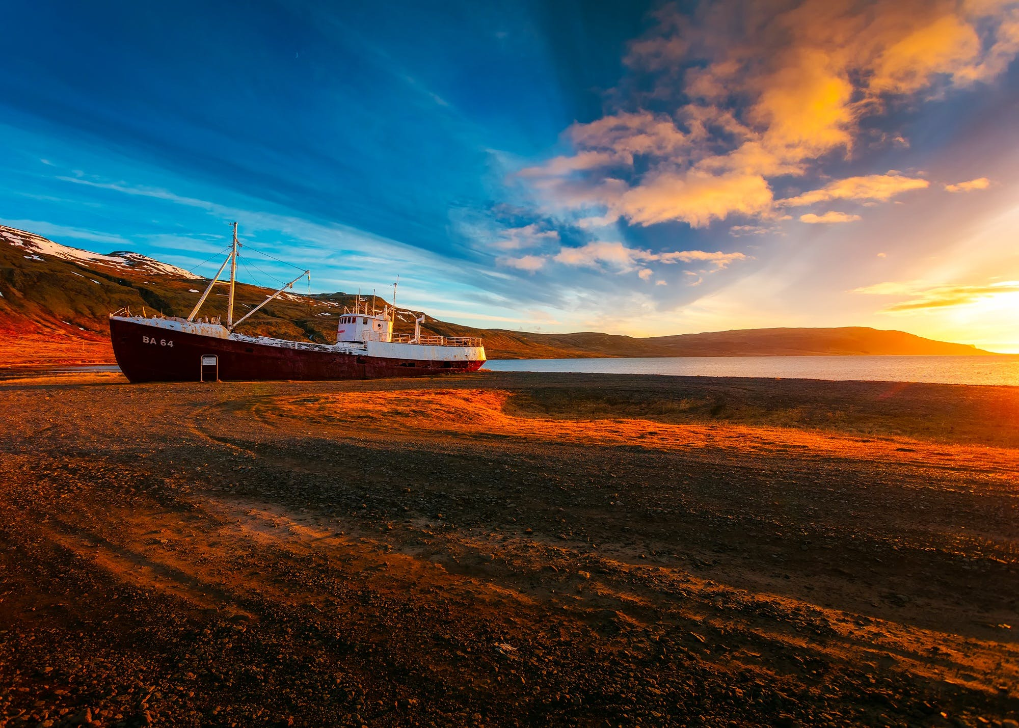 White and Maroon Cargo Ship on Sand