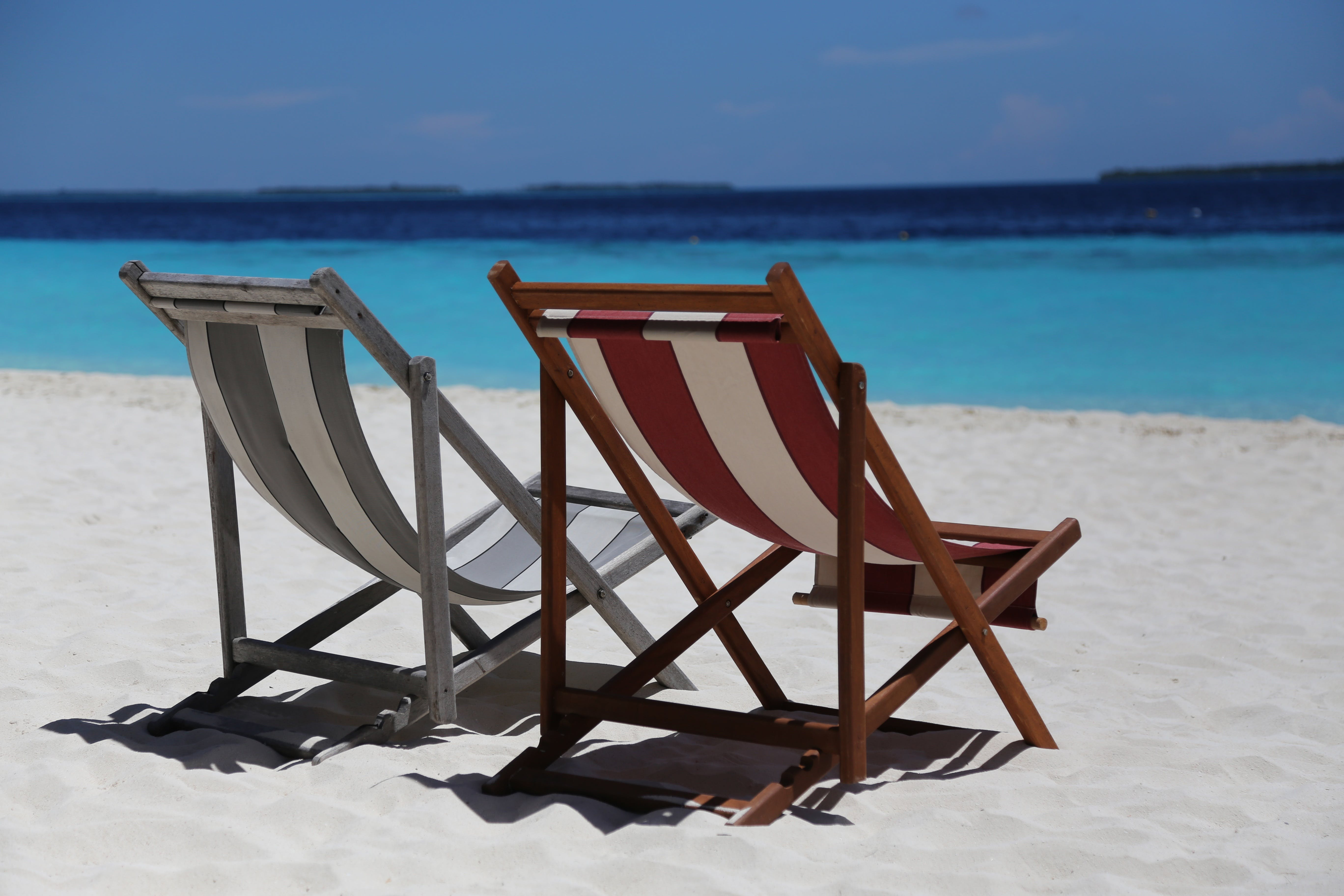 Two Folding Chairs on White Sand Seashore