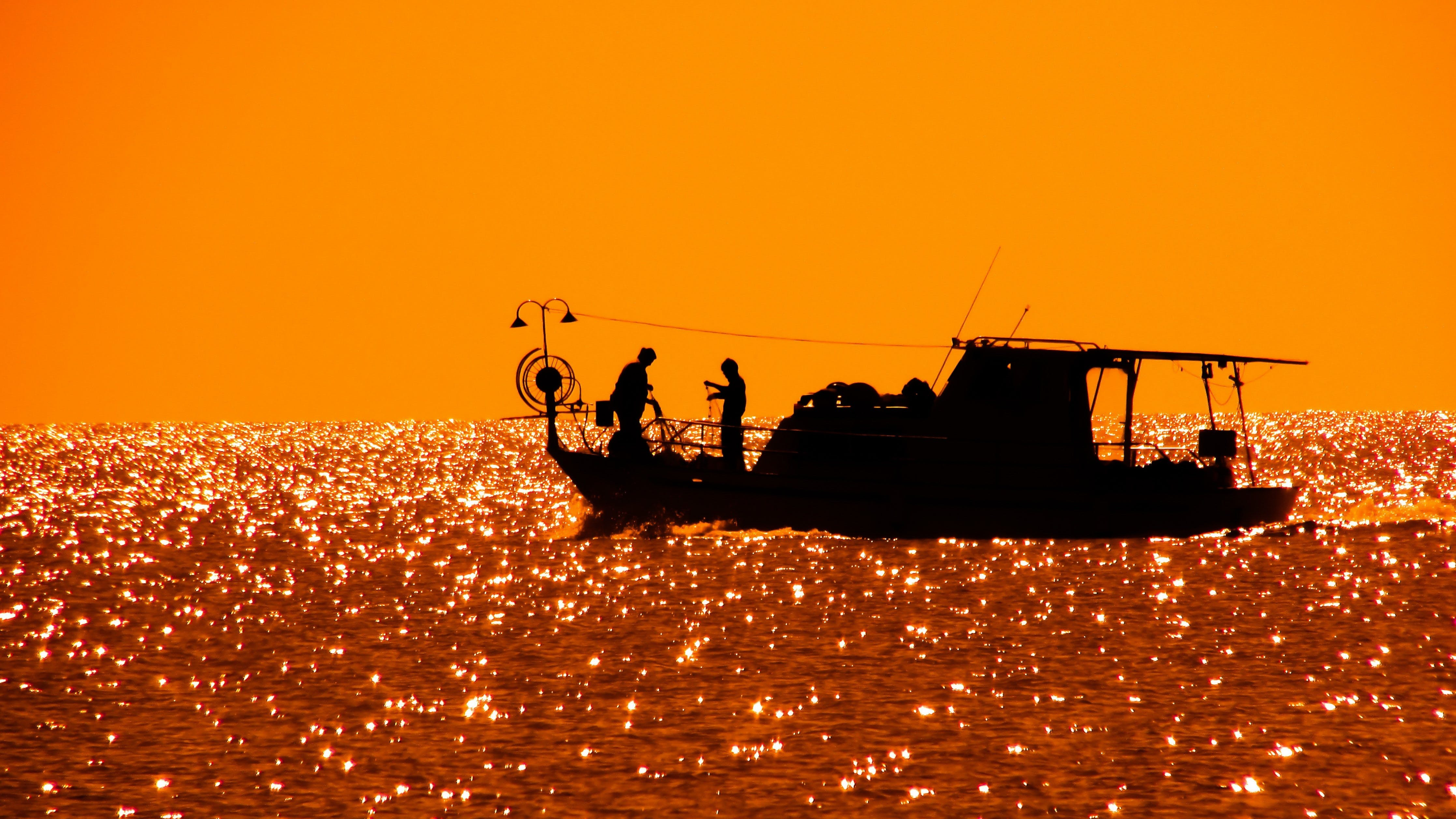 Silhouette of Fishing Vessel Floating on Body of Water
