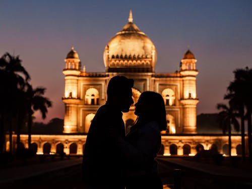 Silhouette of Man Kissing a Woman Near Dome Building