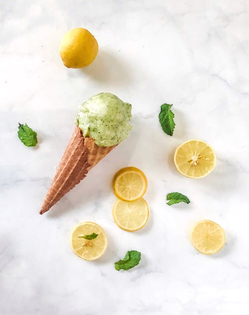 Top view composition of ice cream in waffle cone places near fresh lemon and lemon slices with scattered between green mint leaves on marble surface