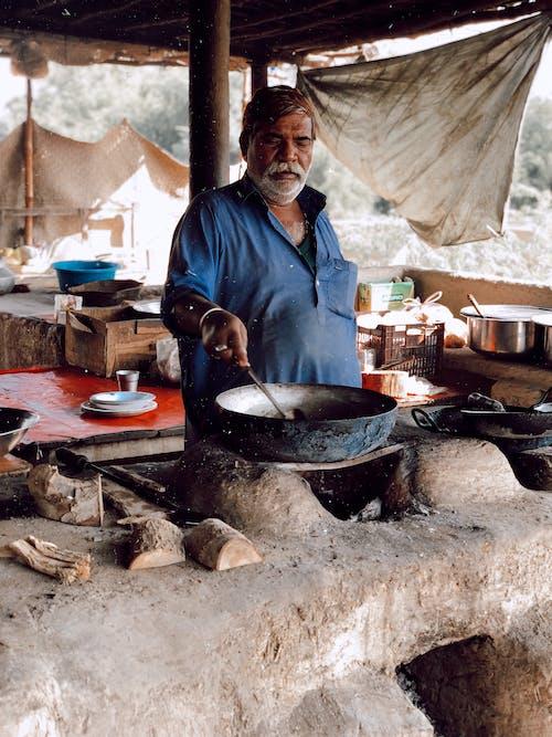在柴火爐後面做飯的男人