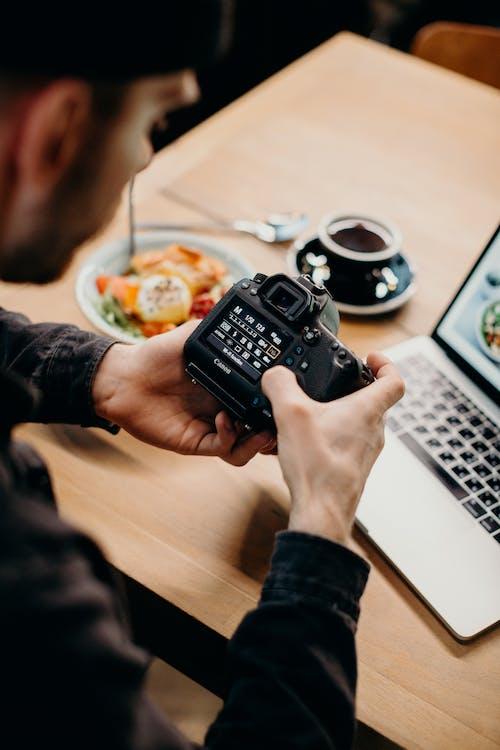 Selective Focus Photography of Man Using Black Dslr Camera