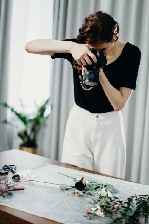 Selective Focus Photography Of Woman Using Black Camera Taking Photos Of Flowers On Table