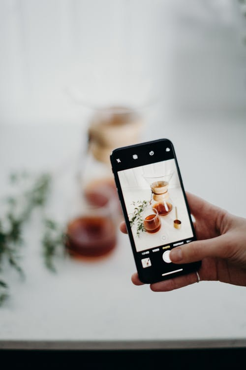Person Taking Photo of Coffee Pot Using Smartphone