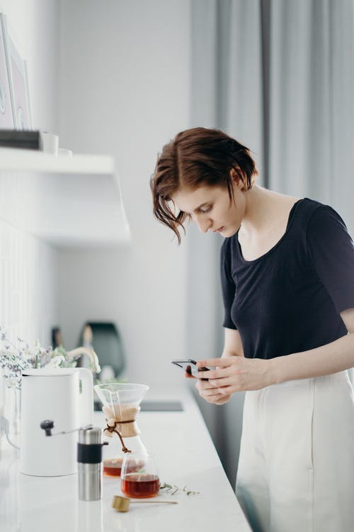 Selective Focus Photography of Woman Using Smartphone Taking Photo of Coffee Pot on Table