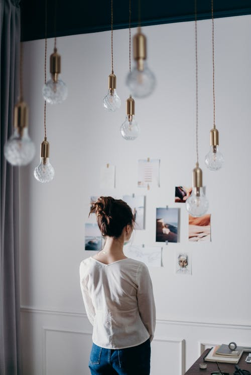 Woman Under Pendant Lights Looking at the Photo on the Wall