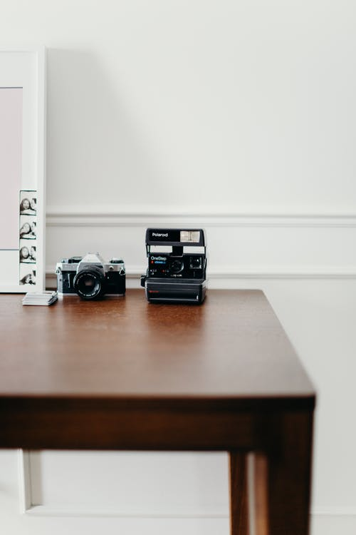 Photo of Polaroid Camera on Wooden Table