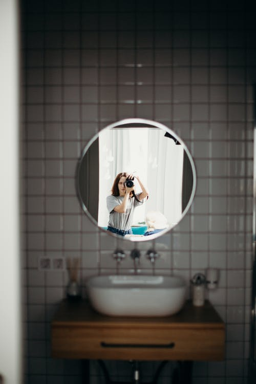 Selective Focus Photography of Woman Taking Photo Reflecting on Mirror