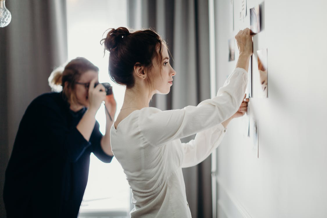 Woman Putting Photo on the Wall