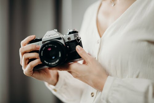 Selective Focus Photography of Person Holding Black and Gray Canon Camera