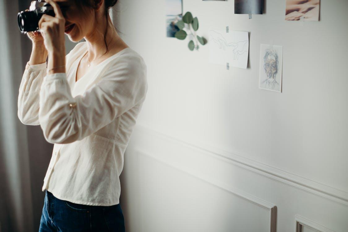 Женщина в белой блузке фотографирует