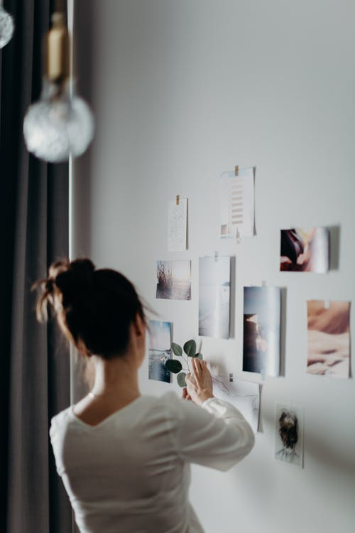 Woman Putting Photo on Wall
